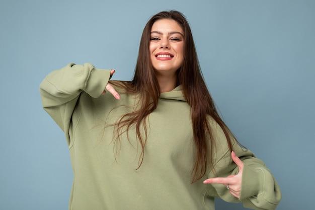 Foto der schönen jungen brünetten coolen frau in einem stylischen khaki-kapuzenpulli einzeln auf blauem hintergrund