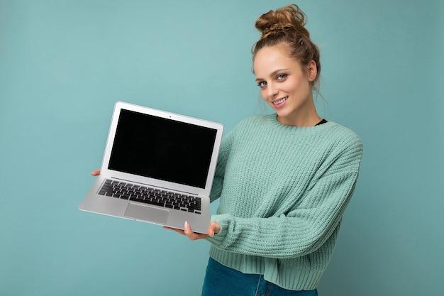Foto der schönen jungen frau, die den computerlaptop hält, der die kamera lokalisiert über buntem hintergrund betrachtet.