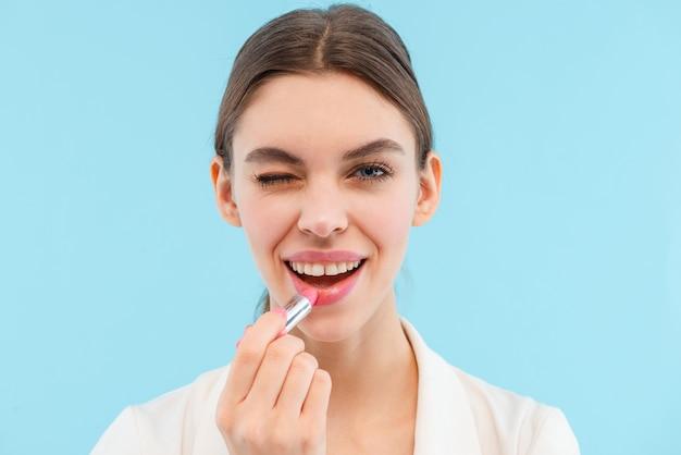 Foto der schönen jungen frau, die isoliertes halten des lippenbalsams aufwirft.