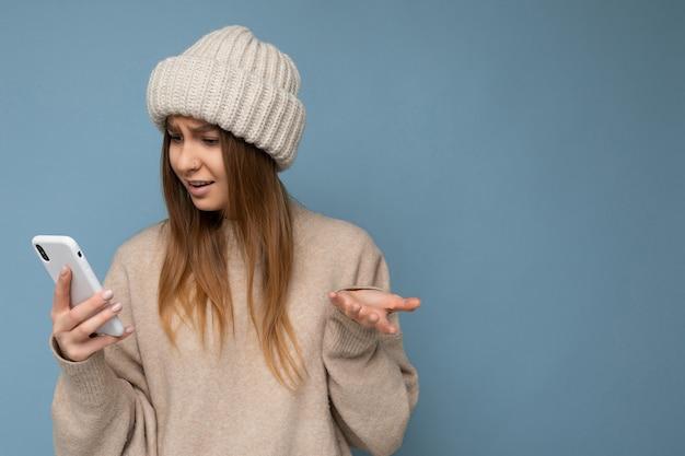 Foto der schönen jungen schockierten blonden frau, die einen stilvollen beige warmen pullover und einen gestrickten winter trägt