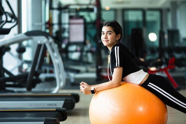 Foto der schönen jungen sportlichen frau. mädchen, das mit fitnessball ausarbeitet