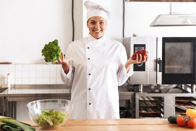 Foto der schönen köchin, die weiße einheitliche kochmahlzeit mit frischem gemüse trägt, in der küche am restaurant