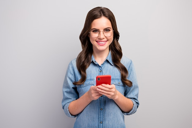 Foto der schönen kreativen dame des freien freiberuflers, die das telefonieren des neuen blogpostens des neuen blogs hält gute laune tragen spezifikationen spezifiziert lässiges jeans-jeanshemd isolierte graue farbe