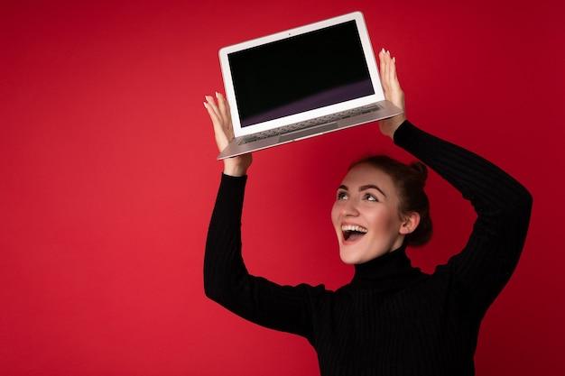 Foto der schönen lächelnden glücklichen jungen brunettefrau, die computerlaptop mit leerem monitor hält
