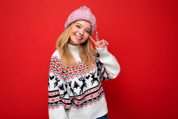 Foto der schönen lächelnden jungen blonden frau mit warmer strickmütze und warmem winterpullover
