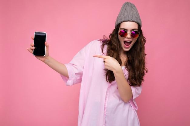 Foto der schönen lächelnden jungen frau gut aussehend, die lässiges stilvolles outfit trägt, das lokal steht