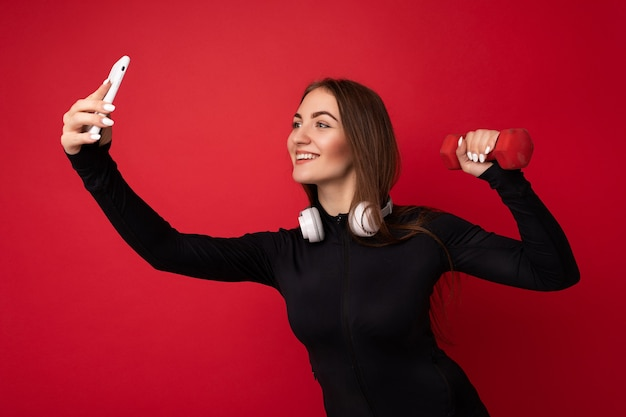 Foto der schönen lächelnden positiven erwachsenen brünetten frau, die schwarze sportkleidung weiß trägt
