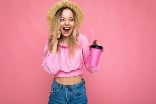 Foto der schönen positiven emotionalen jungen blonden frau, die rosa erntebluse und strohhut trägt