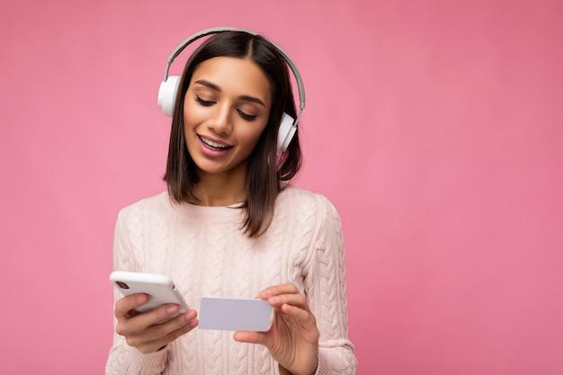 Foto der schönen positiven jungen brünetten frau, die rosa lässigen pullover lokalisiert über rosa trägt