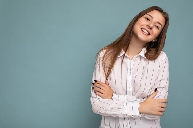 Foto der schönen positiven lächelnden erwachsenen frau, die stilvolle kleidung trägt, die einzeln auf buntem hintergrund mit kopienraum steht und kamera betrachtet.