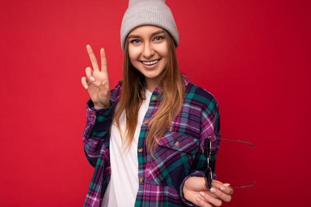 Foto der schönen positiven lächelnden jungen dunkelblonden weiblichen person lokalisiert über rotem hintergrund Premium Fotos