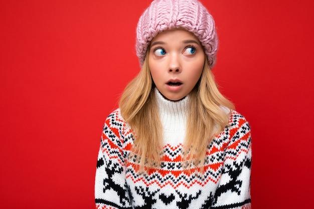 Foto der schönen schockierten jungen blonden frau isoliert über der roten hintergrundwand, die winter trägt