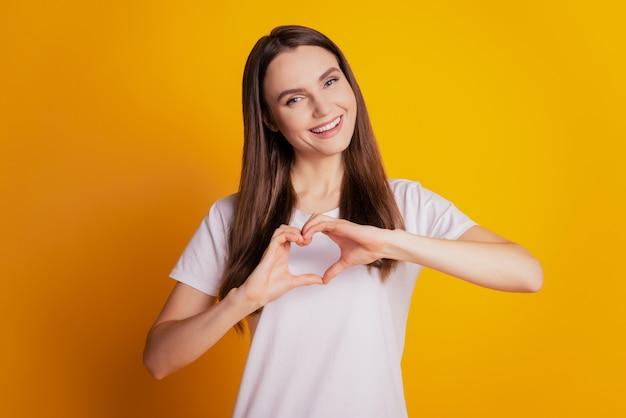 Foto der schönen süßen dame zeigen herzschild tragen weißes t-shirt, das auf gelbem hintergrund posiert