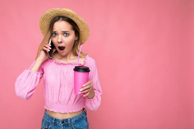 Foto der schönen überraschten emotionalen jungen blonden frau, die rosa erntebluse und strohhut trägt