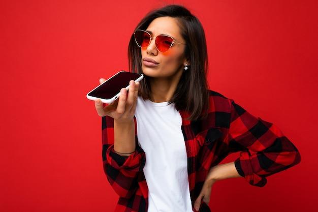 Foto der schönen unzufriedenen jungen brunet-frau, die stilvolles rotes hemd, weißes t-shirt und rotes t-shirt trägt