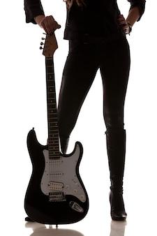 Foto der schwarzweiss-gitarre neben weiblichen beinen in ledergamaschen und -stiefeln. auf weißem hintergrund isoliert