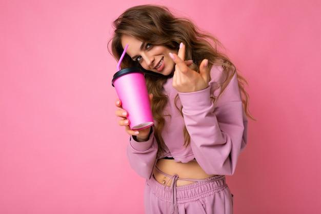 Foto der sexy attraktiven jungen glücklichen lächelnden brünetten frau, die tägliche stilvolle kleidung trägt, die über bunter hintergrundwand lokalisiert wird, die pappbecher für den ausschnitt trinkt tee hält, der kamera betrachtet.