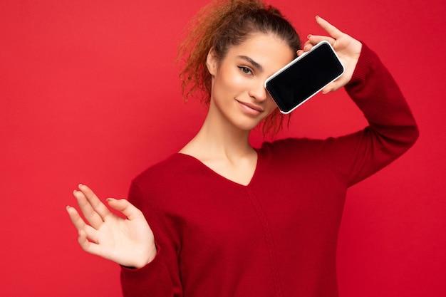 Foto der sexy glücklichen jungen weiblichen person, die dunkelroten pullover lokalisiert über rotem hintergrund hält smartphone hält und handybildschirm mit kopienraum für ausschnitt beim betrachten der kamera zeigt.