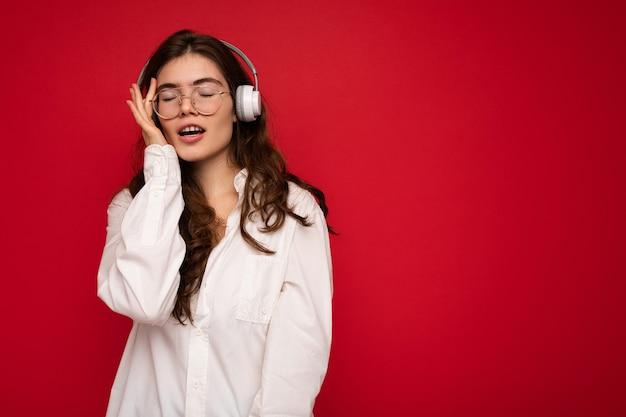 Foto der sexy schönen glücklichen lächelnden jungen brunettefrau, die weißes hemd und optische brille trägt optical