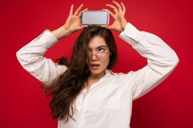 Foto der sexy schönen jungen brünetten frau, die weißes hemd und optische brille lokalisiert trägt