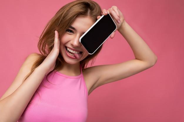 Foto der sexy schönen positiven jungen blonden frau, die rosafarbenes top trägt, das isoliert auf rosa balanciert