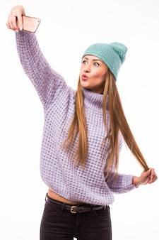 Foto der stilvollen hübschen jungen dame halten telefon lächelnde klebende zunge machen selfies anhänger blogger tragen sonne spezifikationen lässig hut jacke gelber pullover isoliert weiße farbe wand