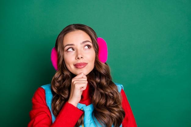 Foto der süßen charmanten jungen dame, die mit dem finger kinn nachdenklich lächelt, den leeren raum denkt, das skigebiet trägt rosa ohrwärmer blaue weste roter pullover isoliert grüner farbhintergrund