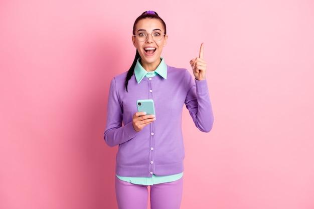 Foto der süßen frau, die das telefon direkt mit dem finger nach oben offenem mund hält, tragen spezifikationen violette strickjacke isoliert rosafarbener hintergrund