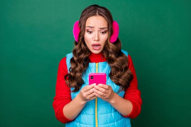 Foto der süßen lieben jungen dame mit offenem mund halten telefon lesen schlechte gefälschte nachrichten coronavirus-opferrate erhöhte rosa ohrwärmer blaue weste roter pullover isoliert grüner hintergrund