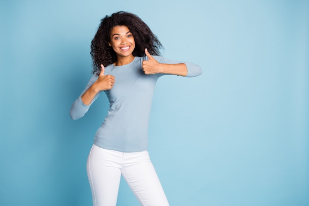 Foto der trendigen fröhlichen positiven netten hübschen freundin, die positives feedback über waren hinterlässt, die sie gekauft hat, zahnend lächelnd zeigt daumen hoch isolierten pastellblauen farbhintergrund