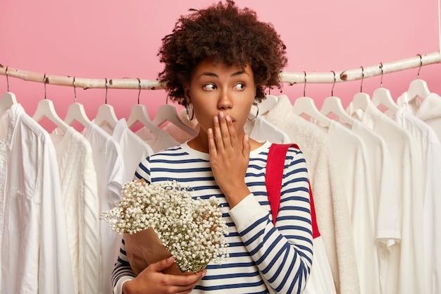 Foto der überraschten afroamerikanischen käuferin bedeckt mund und schaut zur seite, gekleidet in gestreifte kleidung, hält blumenstrauß, steht gegen weiße outfits, die in einer reihe auf schienen hängen, isoliert auf rosa