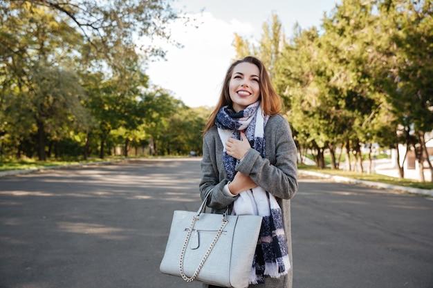 Foto der unglaublichen glücklichen dame, die über naturhintergrund lächelt und tasche hält. sieh zur seite.