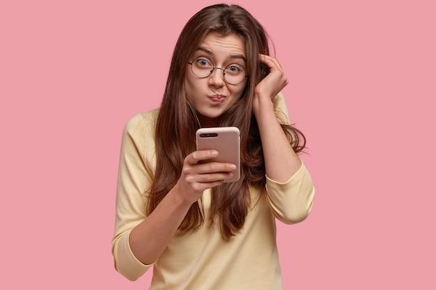 Foto der unzufriedenen dame spitzt lippen und schaut mit ahnungslosem ausdruck, hält handy, surft im internet, schaut auf bildschirm, liest verwirrte nachrichten