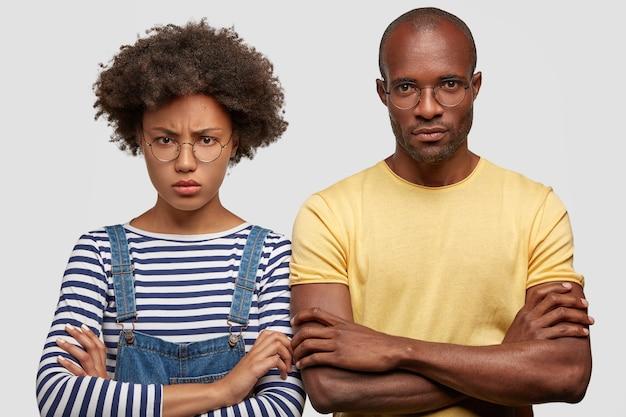 Foto der unzufriedenen mürrischen afroamerikanischen studentin und ihres männlichen begleiters