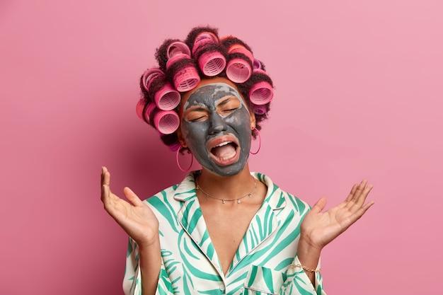 Foto der unzufriedenen weinenden hausfrau fühlt sich müde und erschöpft, trägt lockenwickler und schönheitsgesichtsmaske, spreizt handflächen, gekleidet in freizeitkleidung, isoliert auf rosa. kosmetologie, spa-behandlung