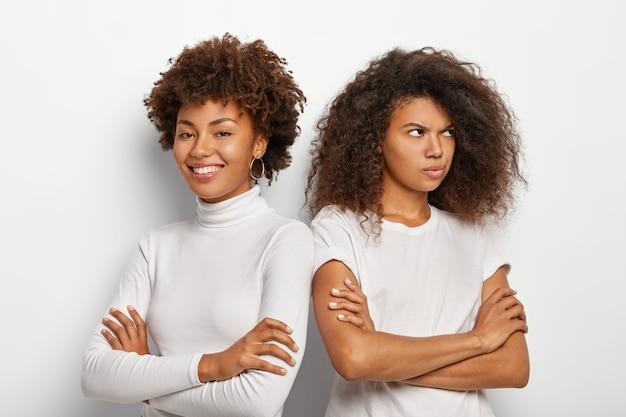 Foto der unzufriedenheit afro frau dreht sich von freund, hält arm gefaltet, gekleidet in lässiges outfit, pose vor weißem hintergrund. zwei schwestern haben missverständnisse