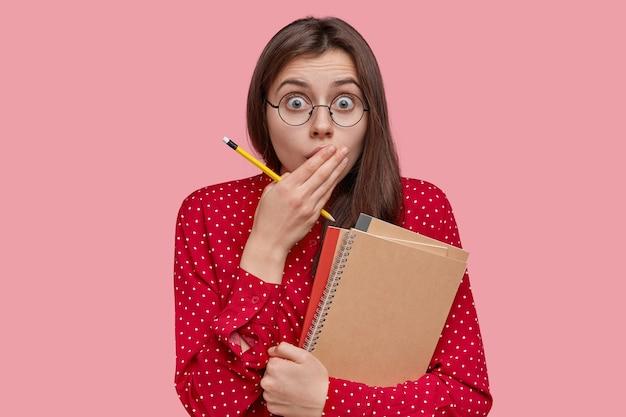 Foto der verängstigten jungen frau mit dunklem haar bedeckt mund, hat ausdruck überrascht, verwendet notizblock zum schreiben von aufzeichnungen