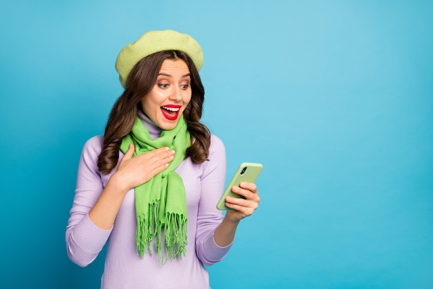 Foto der verblüfften verrückten dame halten telefon lesen beitrag kommentare neue follower abonnenten tragen grüne baskenmütze lila rollkragen schal hose isoliert blau farbe wand