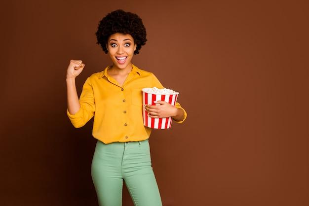 Foto der verrückten dunklen haut wellige dame halten popcorn eimer essen hühneraugen sehen fußballspiel unterstützung lieblingsteam tragen gelbes hemd grüne hose isoliert braune farbe