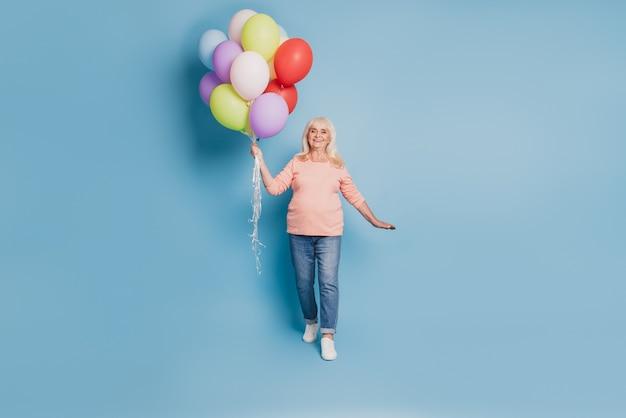 Foto der verträumten rentnerin, die viele luftballons in rosa pullover auf blauem hintergrund hält