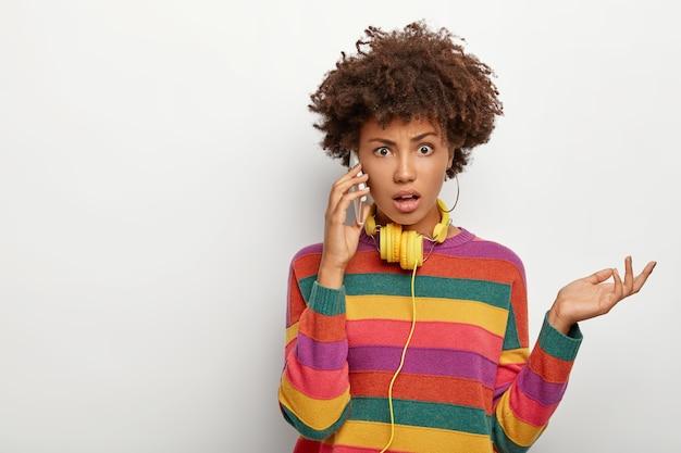 Foto der verwirrten empörten afroamerikanerin hebt handfläche, spricht über handy, gekleidet in freizeitkleidung, sieht unglücklich aus, posiert vor weißem hintergrund.