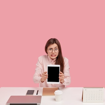 Foto der verwirrten jungen frau hält touchpad mit mock-up-bildschirm, verwendet anwendung, trägt transparente brille