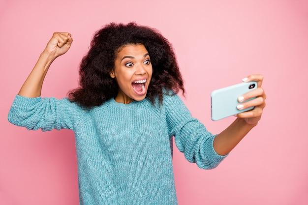 Foto der verzogenen verrückten aufgeregten überglücklichen frau, die schreit, nachdem sie das niveau im spiel abgeschlossen hat, isolierte rosa pastellfarbwand