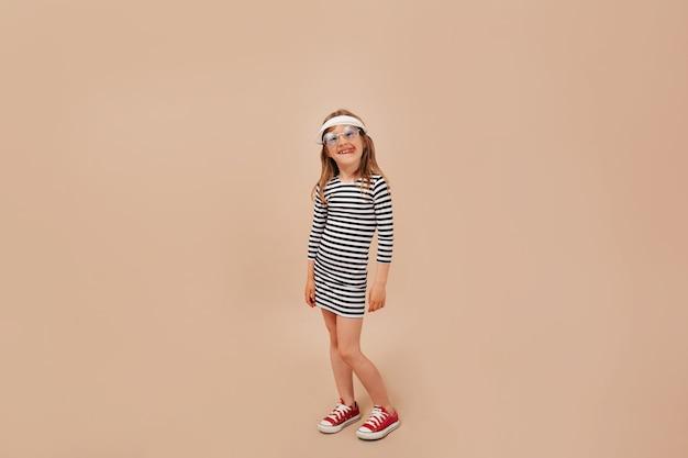 Foto der vollen länge des niedlichen charmanten kleinen mädchens, das kleid, mütze und turnschuhe trägt, die an der kamera über beigem hintergrund aufwerfen