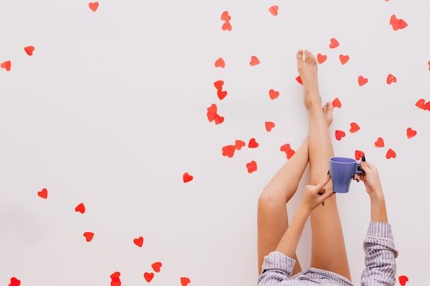 Foto der weiblichen beine auf rotem konfetti