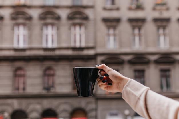 Foto der weiblichen hand mit der schwarzen tasse des heißen getränks