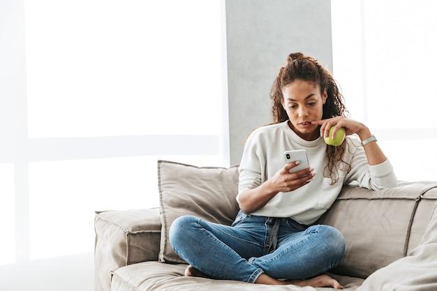 Foto der zufriedenen afroamerikanerfrau, die handy benutzt, während sie auf couch in heller wohnung sitzt