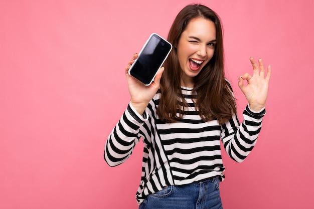 Foto der zwinkernden schönen glücklichen jungen frau mit gestreiftem pullover, die über dem hintergrund isoliert ist, mit kopienraum, der eine ok geste zeigt, die auf die kamera schaut, die den handy-bildschirm zeigt. mock-up, ausschnitt