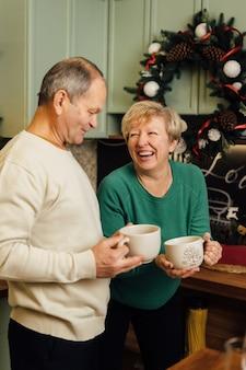 Foto des älteren paares der 60er jahre, das das leben in der küche mit kaffeetassen genießt. st. valentinstag von