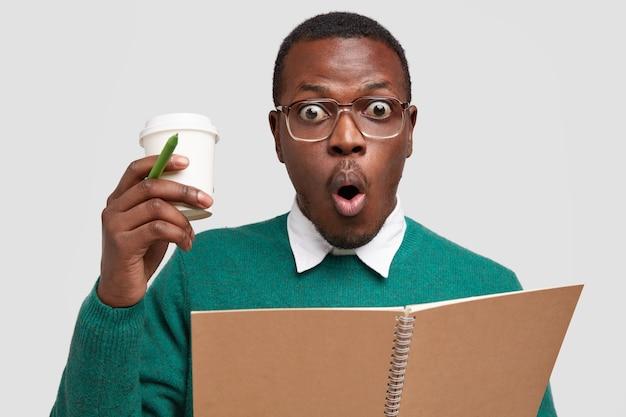 Foto des ängstlichen emotionalen schwarzen kerls sieht in der betäubung aus, trägt kaffee zum mitnehmen, schreibt notizen in notizbuch, hält mund rund, lässig gekleidet
